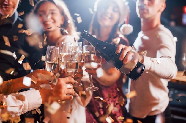 Grupo de amigos alegres celebrando el año nuevo en el interior con bebidas en las manos.