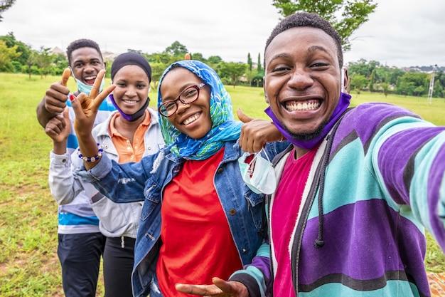 Grupo de amigos alegres con mascarillas tomando un selfie en un parque