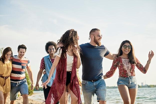 Grupo de amigos alegres en la playa