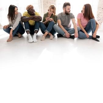 Grupo de amigos de ángulo bajo en el piso