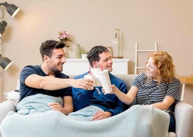Grupo de amigos animando con refrescos en casa