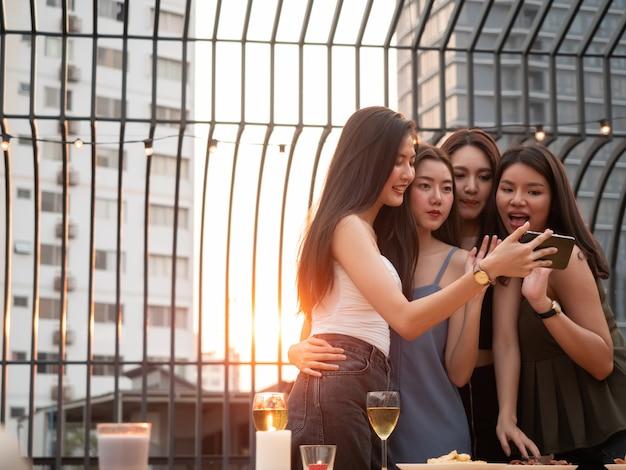 Grupo de amigos asiáticos animando y bebiendo en la fiesta de la terraza. jóvenes disfrutando y pasando el rato en la azotea al atardecer