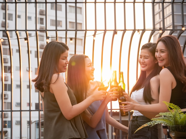 Grupo de amigos asiáticos animando y bebiendo en la fiesta de la terraza. jóvenes tostando vidrio con cerveza en el restaurante de la azotea