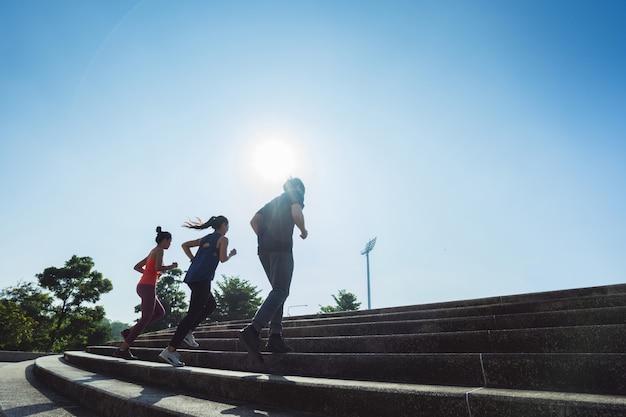 Grupo de amigos asiáticos corriendo por las escaleras