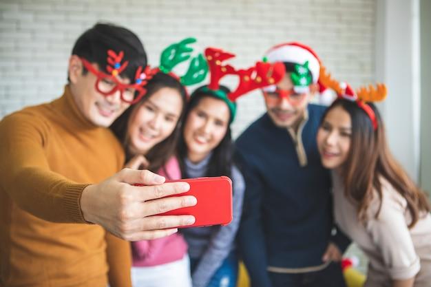 Grupo de amigos asiáticos tomando selfie con un amigo juntos por teléfono inteligente en casa durante la fiesta de víspera de navidad o fiesta de año nuevo. feliz invierno navidad y feliz año nuevo concepto de fiesta