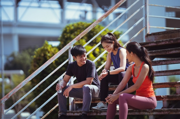 Grupo de amigos asiáticos trotando por la mañana, conversan, se sientan y descansan