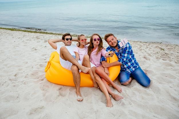 Grupo de amigos atractivos, sentados juntos en el sofá de aire lamzac, tomando un selfie