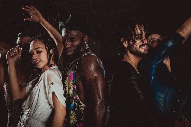 Grupo de amigos bailando bajo la lluvia