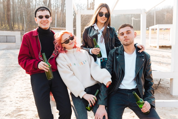 Grupo de amigos bebiendo cerveza y divirtiéndose juntos