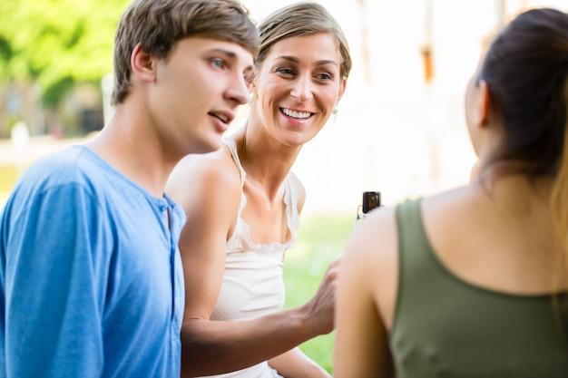 Grupo de amigos bebiendo cerveza en el lago
