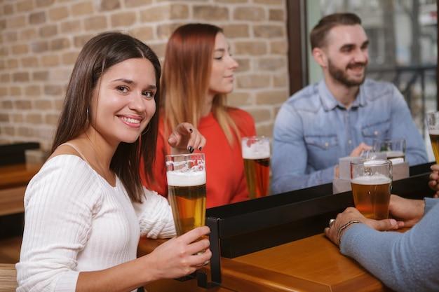 Grupo de amigos bebiendo cerveza en el pub juntos