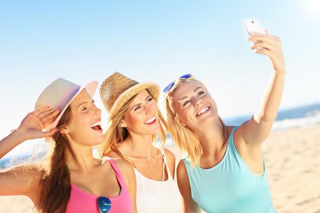 Grupo de amigos bebiendo cerveza y tomando selfie en la playa
