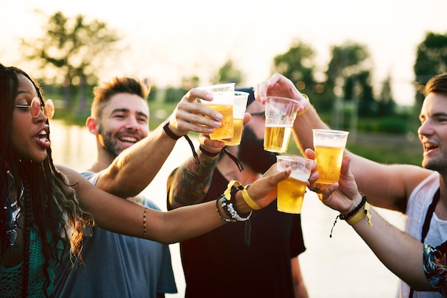 Grupo de amigos bebiendo cervezas disfrutando del festival de música juntos