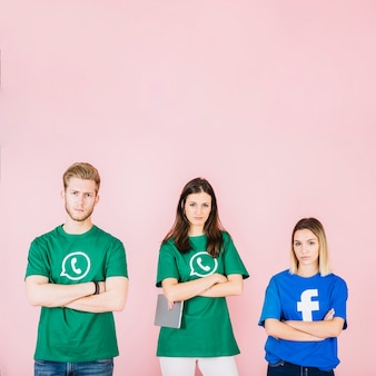 Grupo de amigos con los brazos cruzados sobre fondo rosa