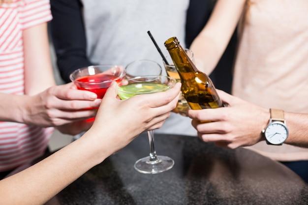 Grupo de amigos brindando con cerveza y cócteles