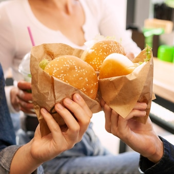 Grupo de amigos brindando con hamburguesas