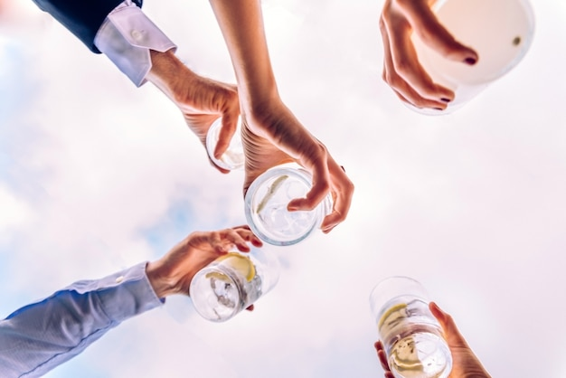 Grupo de amigos brindando con unos vasos de alcohol con el cielo de fondo