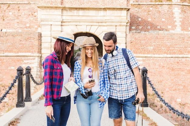 Grupo de amigos buscando localización en mapa.