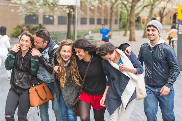 Grupo de amigos caminando y divirtiéndose juntos en londres