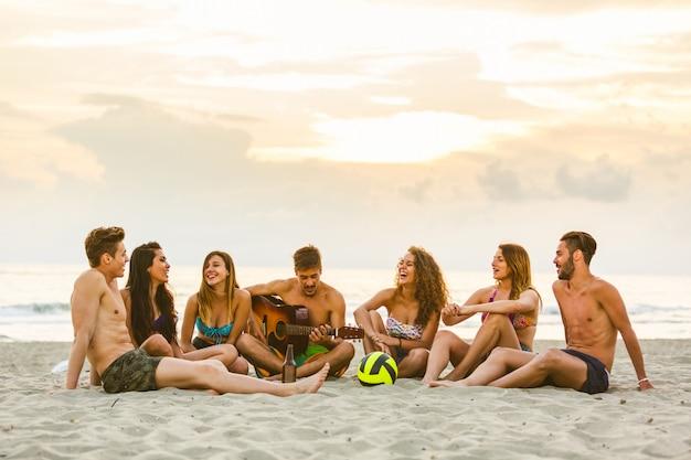 Grupo de amigos cantando en la playa