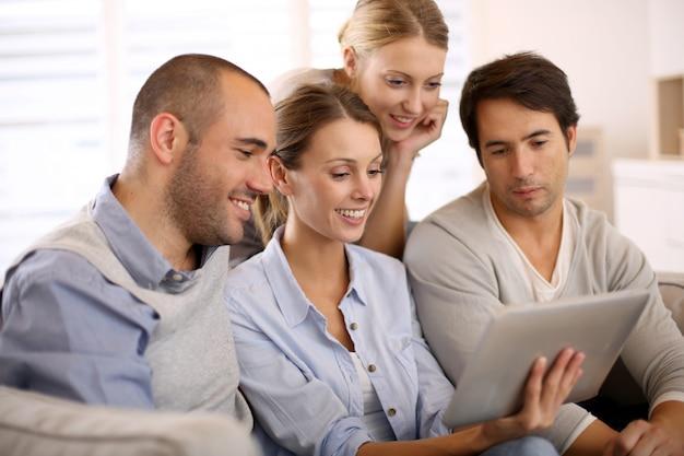 Grupo de amigos en casa usando tableta en sofá