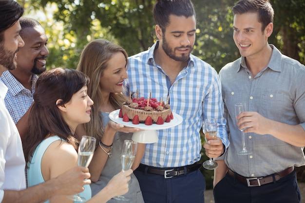 Grupo de amigos celebrando el cumpleaños de la mujer en el restaurante al aire libre