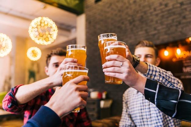 Grupo de amigos celebrando el éxito con vasos de cerveza.