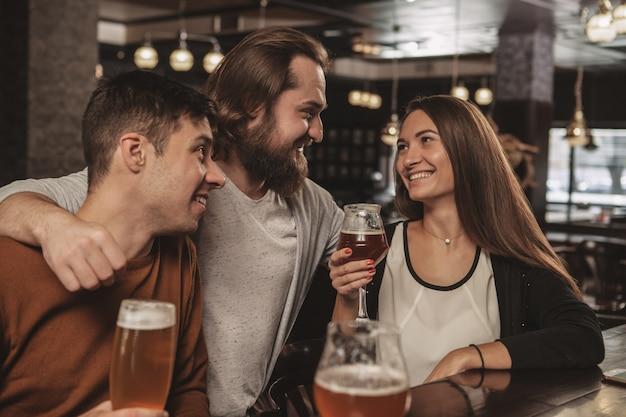 Grupo de amigos celebrando en el pub, bebiendo cerveza juntos
