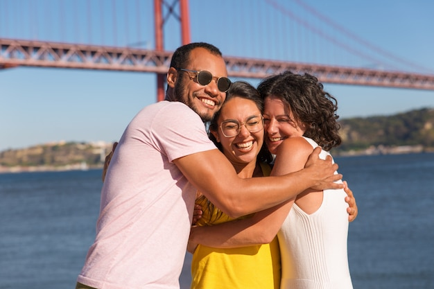 Grupo de amigos cercanos felices saludando y abrazándose