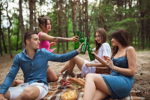 Grupo de amigos chocan botellas de cerveza durante el picnic en el bosque de verano
