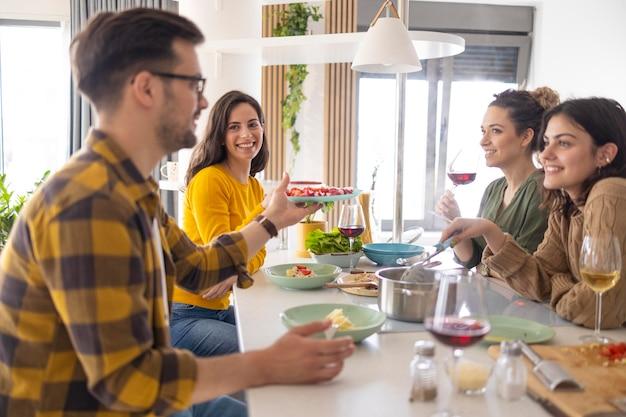 Grupo de amigos comiendo pasta juntos en la cocina