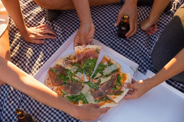 Grupo de amigos comiendo pizza al aire libre