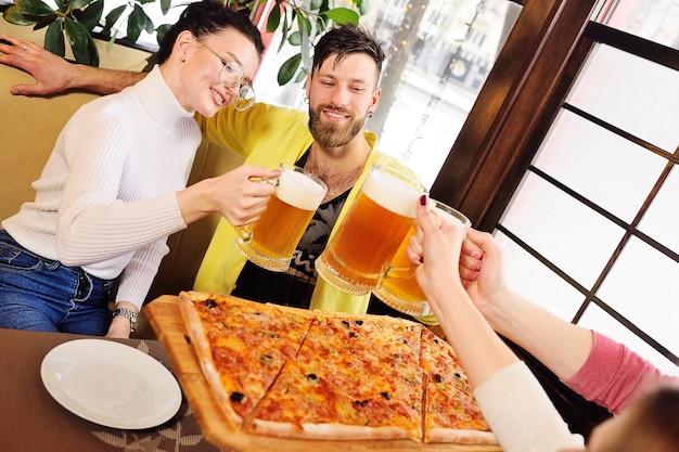 Grupo de amigos comiendo pizza y bebiendo cerveza en el bar o en la cafetería