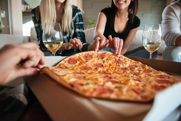 Grupo de amigos comiendo pizza grande y bebiendo