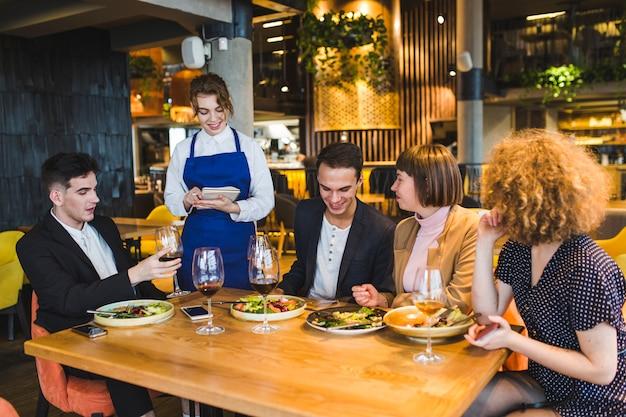 Grupo de amigos comiendo en restaurante
