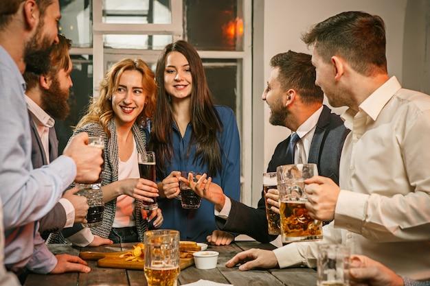 Grupo de amigos disfrutando de bebidas con cerveza por la noche