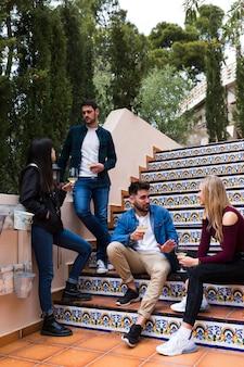 Grupo de amigos disfrutando de bebidas en la escalera