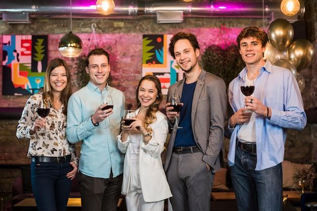 Grupo de amigos disfrutando de bebidas por la noche en el bar