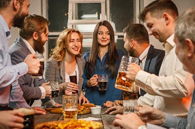 Grupo de amigos disfrutando de bebidas por la noche con cerveza en la mesa de madera