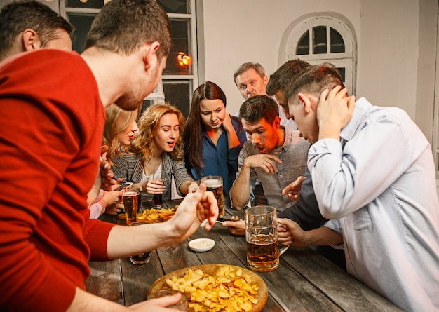 Grupo de amigos disfrutando de bebidas por la noche con cerveza