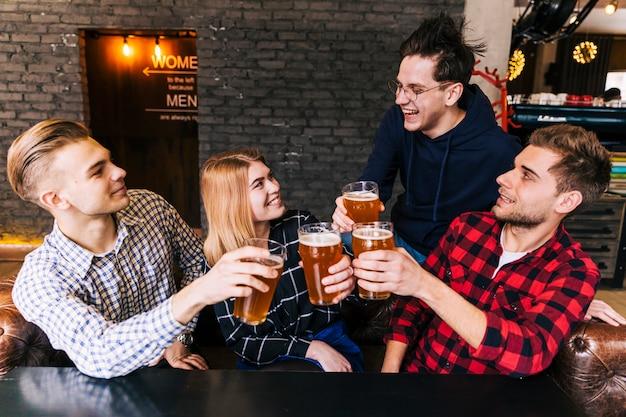 Grupo de amigos disfrutando de la cerveza en pub.