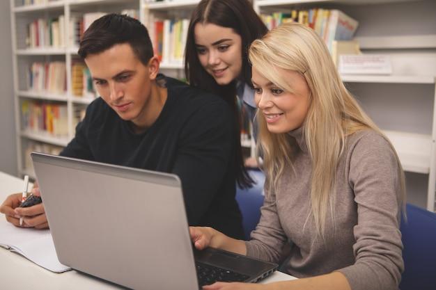 Grupo de amigos disfrutando de estudiar juntos en la biblioteca