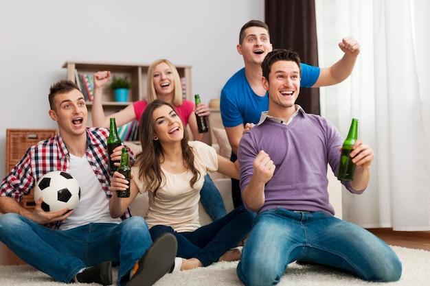 Grupo de amigos disfrutando del fútbol en la televisión