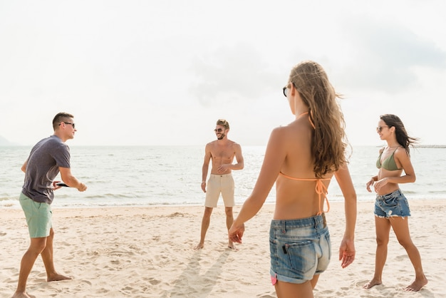 Grupo de amigos disfrutando jugando a la playa juntos