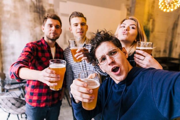Grupo de amigos disfrutando de la selfie disfrutando de la cerveza en pub.