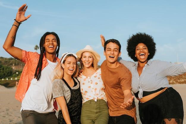 Grupo de amigos diversos pasando el rato en la playa.
