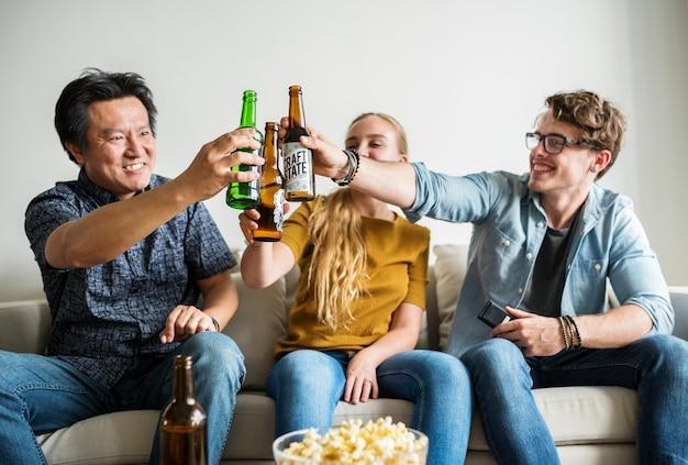 Grupo de amigos diversos que tienen una noche de cine bebiendo cerveza.
