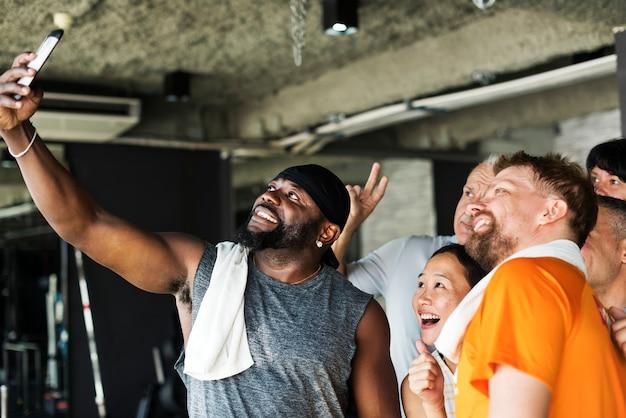 Grupo de amigos diversos que toman selfie juntos en el gimnasio