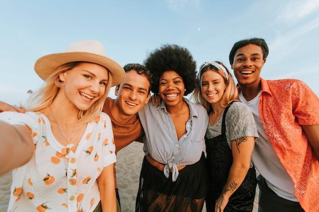 Grupo de amigos diversos que toman un selfie en la playa.
