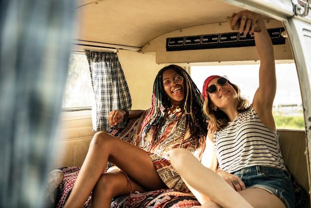 Grupo de amigos diversos que toman selfie en un viaje en automóvil juntos